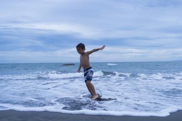 Boy run around in the swimsuit on the beach