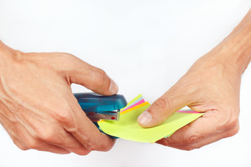 Hands fastened colored blanks stapler on a white background