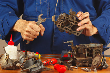 Repairman repairing parts of old automobile engine