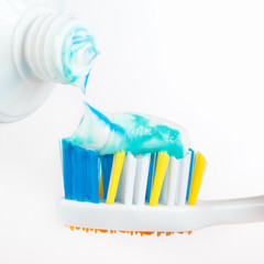 Color fresh toothpaste on a toothbrush close up