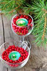 Candles in glasses with cranberries