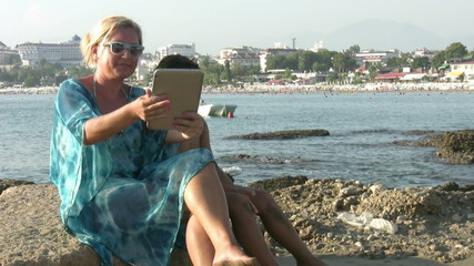 Mother and son   on beach taking selfie