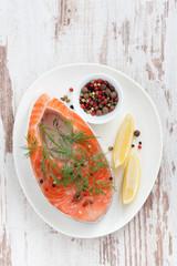 fresh salmon steak, lemon and pepper on white wooden background