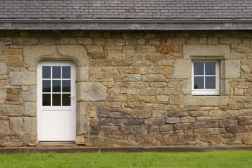 Modernisierte Granitfassade mit Kunststofftür und –fenster