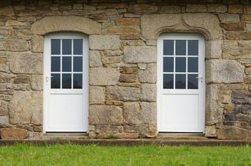 Modernisierte Granitfassade mit zwei Kunststofftüren