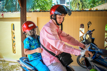 father and son wearing helmets are going to go on a motorbike in