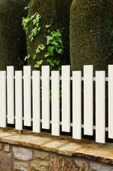 PVC-Zaun auf Natursteinmauer vor Zypressenhecke