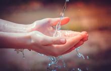 Kobiece dłonie z plusk wody