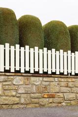 PVC-Zaun auf Natursteinmauer vor kunstvoller Zypressenhecke