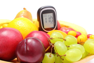 Fresh fruits and glucose meter on wooden plate