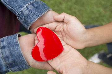 Children holding a red heart