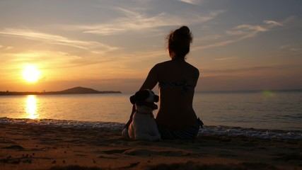 Female Silhouette with Dog at Sunset on the Beach. Slow Motion.