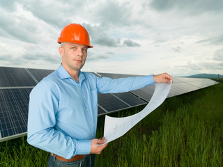 man holding solar panel station plans