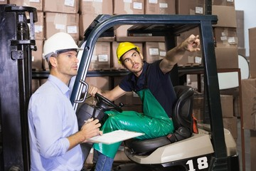 Warehouse manager talking with forklift driver