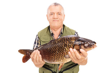 Mature fisherman holding a freshwater fish