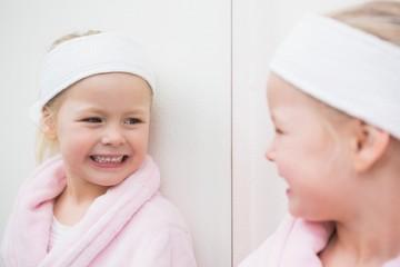 Cute little girl looking in mirror