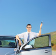Man holding a car key on an open road
