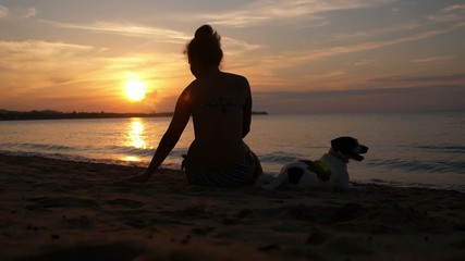 Woman Silhouette with Dog at Sunset on Sandy Beach. Slow Motion.