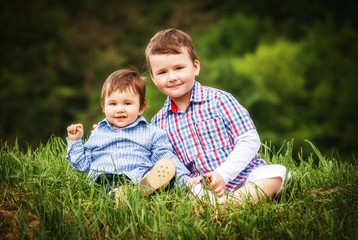 two little smiling child boy brothers walking outdoor