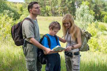 Happy hiking couple with son looking at the map.
