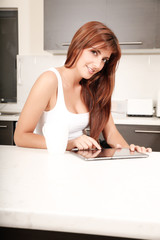Frau mit Tablet PC in der Küche