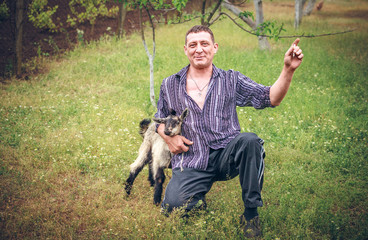 Portrait of male farmer holding goat