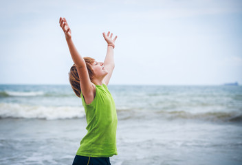 boy with raised hands on the seashore