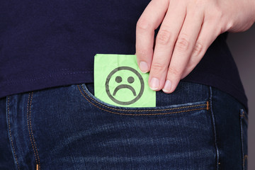 Paper note with sad face in a pocket of jeans