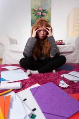 Sad girl among notes for exam