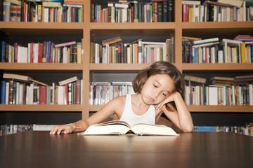Niña estudiando junto a librería con gesto de fastidio