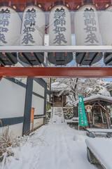 冬の雪に覆われた上山の薬師堂の惣門と参道と足湯