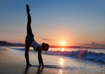 Fitness woman working out at the beach during sunrise