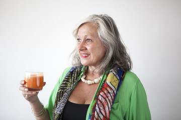 Mature woman drinking carrot juice