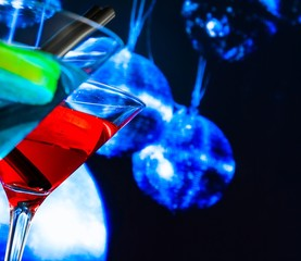 red and blue cocktail with sparkling disco ball background