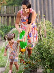 mother and baby watering vegetables in the garden