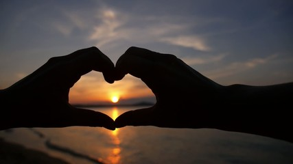 Silhouette Hand in Heart Shape during Sunset. Slow Motion.
