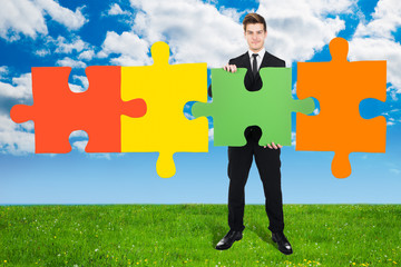 Confident Businessman Solving Jigsaw Puzzle On Field