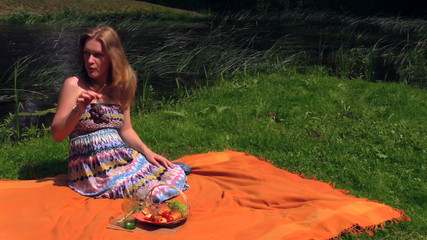 Beautiful pregnant woman girl eat grapes sit on plaid near river