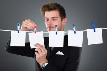 Businessman Pinning Blank Papers On Clothesline