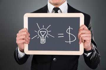 Businessman Holding Slate With Idea Equation