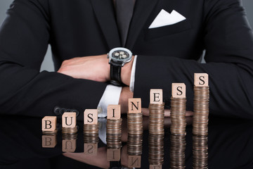 Businessman With Business Blocks On Stacked Coins