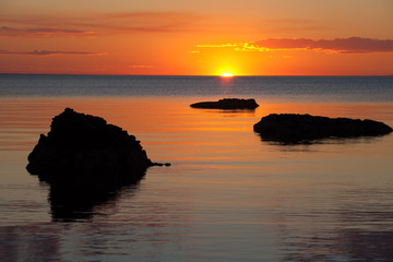 Vivid orange sunset over water, with rock silhouettes