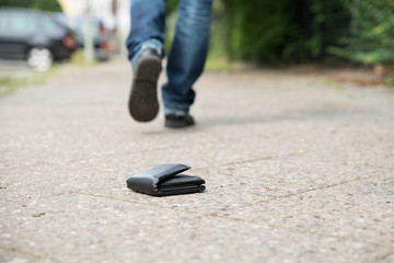 Man Walking Against Fallen Wallet On Street