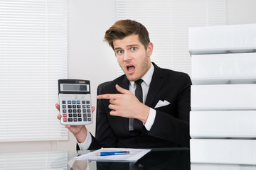 Shocked Businessman Looking At Calculator