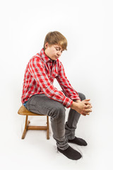 sad looking young boy with red shirt sitting on a wooden school
