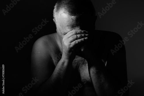 Sad man with hands on face over black - 70083689