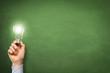 Hand hält Lampe vor der Tafel / Idee / Konzept