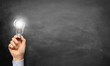Hand holding Light Bulb / Blackboard - 70084673