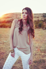 Beautiful brunette lady in field at sunset