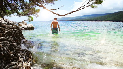 Young man enter in blue bay water on clean Croatian shore
